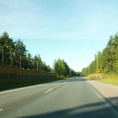 Riksväg 25 i Langansböle, ett bullerskydd i trä syns till vänster, en skylt om kameraövervakning till höger.