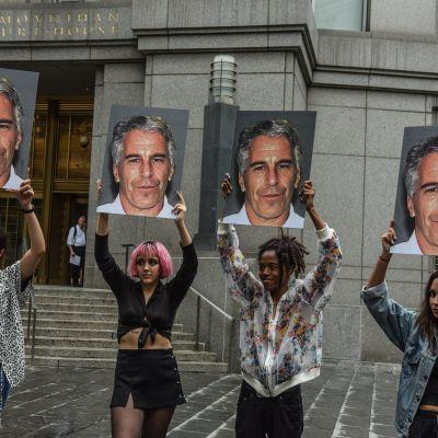 """En protest mot Jeffery Epstein utanför ett tingshus i New York. Protestgruppen """"Hot Mess"""" håller upp förstorade närbilder av Epstein."""