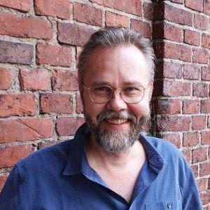 Kuvataiteilija Heikki Marila, harmaapartainen hymyilevä mies pukeutuneena siniseen kauluspaitaan.