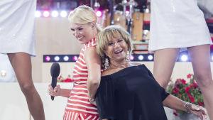 Två kvinnor står på en scen och sjunger medan de lutar sig mot varandra