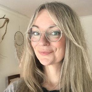 En närbild av en kvinna med långt hår och glasögon med vita skalmar.