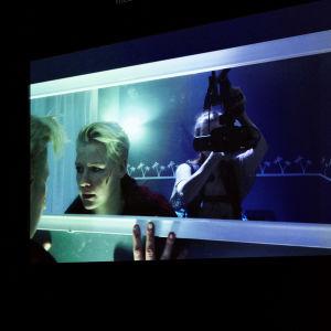 En skådespelare ser in i en spegel. Bakom henne står en kvinna med en videokamera som syns i halvfigur spegeln.