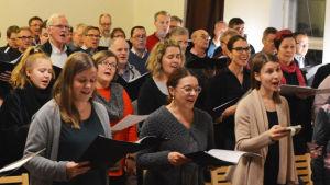Många kvinnoir och män står i en sal. De håller i nothäften och sjunger.