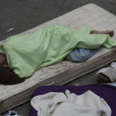 En funktionsnedsatt syrisk flykting sover på polistationens gård på ön Kos i väntan på sina dokument den 7 maj 2015.