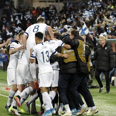Finlands herrlandslag i fotboll firar ett mål i en klunga.