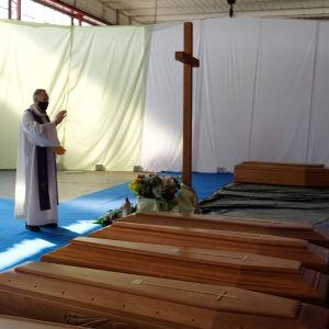 En präst välsignar en rad kistor i ett tält under coronaepidemin i norra Italien