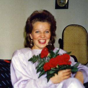 Teologian maisteri Mari-Anna Auvinen ruusukimpun kera valmistujaisjuhlissaan