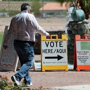 Arizona-man på väg in i vallokal, förbi reklamskyltar.