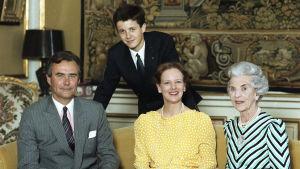 En man och två kvinnor sitter i en soffa, en ung man lutar sig mot ryggstödet