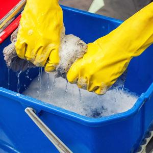 Två händer i gula gummihandskar vrider vatten ur en luddig golvmopp ner i en blå hink.