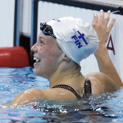 En glad Fanny Teijonsalo i vit badmössa blickar upp mot resultattavlan efter målgång.