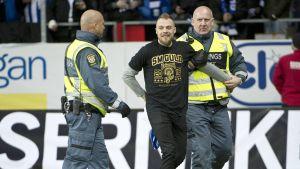 Mats Rosseli Olsen förs bort efter att ha stormat planen.