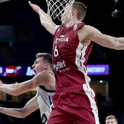 Luka Doncic och Kristaps Porzingis i duell under korgen.