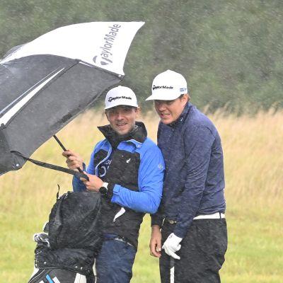 Sami Välimäki (oik.) ja caddie Väinö Viitaharju sateen suojassa Walesissa Euroopan kiertueella.