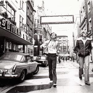 Nuori mies kävelee Lontoon kadulla vauhdikkaasti 1970-luvulla.