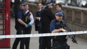 beväpnade polisen står vid ett avspärrningsband, efter gripandet av en terrormisstänkt i London.