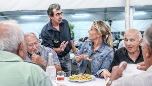 Ella Kanninen isossa ruokapöydässä sammakkofestivaaleilla italialaisten miesten ympäröimänä.