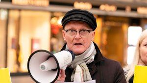 Amnesty Finlands verksamhetsledare Frank Johansson står och talar i en megafon.
