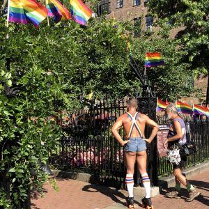 Två män vid ingången till Christopher-parken där den homosexuea frigörelsen anses ha oganiserats för 50 år sedan.