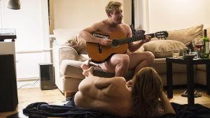Rasmus spelar gitarr sittande naken på soffan medan Marie ligger - naken - på golvet och lyssnar.