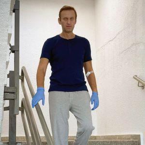 Aleksej Navalnyj går i trappan med ljusblåa plasthandskar på händerna.