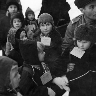 Ruotsiin lähteviä sotalapsia laput kaulassa, noin 5-vuotias tyttö katsoo viattomasti suoraan kameraan.