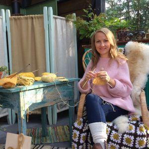 Nainen istuu tuolissa neulomassa. Pöydälla on lisää neuleprojekteja.