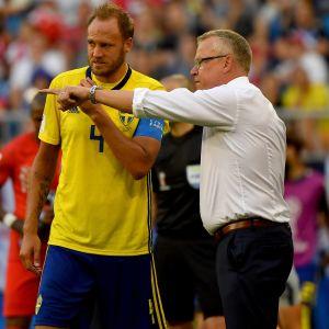 Janne Andersson i vit skjorta förklarar saker för sin gulklädda spelare Andreas Granqvist.