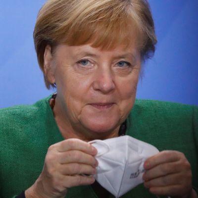 Angela Merkel håller på att sätta på sig ett munskydd.