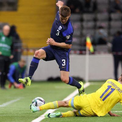 Albin Granlund pomppaa ylöspäin, kun Kazakstanin Yan Vorogovskiy liukuu hänen jaloistaan pallon ohi sivurajan.