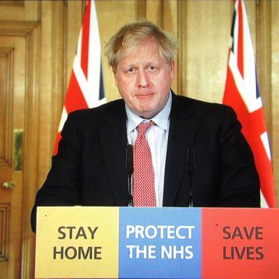 Boris Johnson tiedotustilaisuudessa 25. maaliskuuta 2020. Johnsonilla on todettu koronavirustartunta, ja lieväoireisen pääministerin kerrotaan jatkavan töitä eristyksestä.