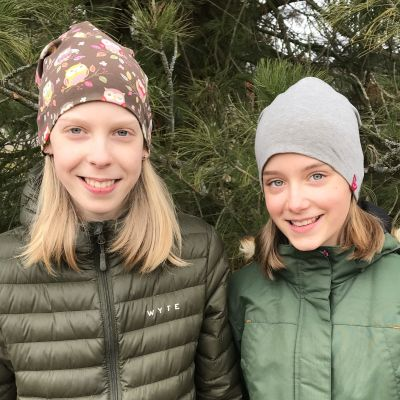 Två flickor står utomhus och ler medan de tittar in i kameran. De är klädda i jacka och mössa.