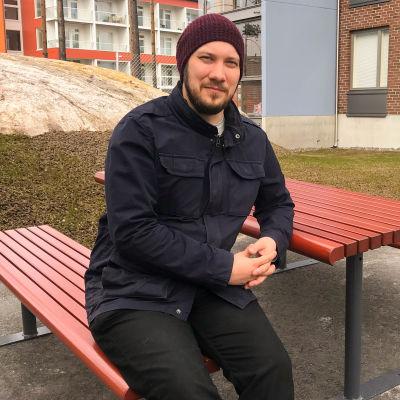 En man som sitter vid ett bord utomhus.