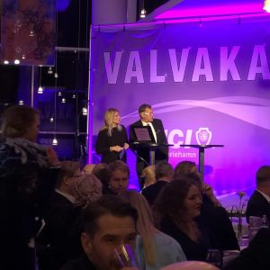 Valanalytiker och publik i violett belysning på valvakan i Mariehamn.