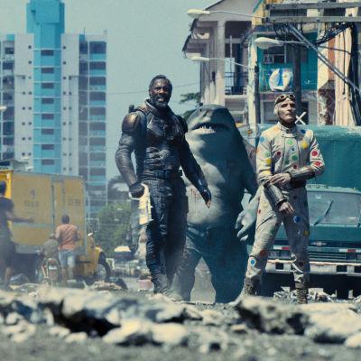 Fyra personer och en hajmänniska står i ett demolerat stadslandskap.