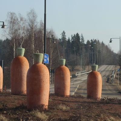 Statyer av morötter som sticker upp ur marken inuti en rondell.