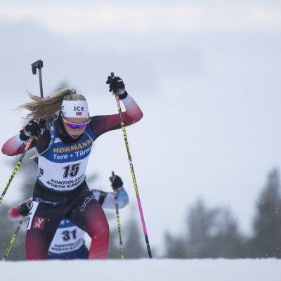 Ingrid Landmark Tandrevold hiihtää ylämäkeä pyssy selässään.