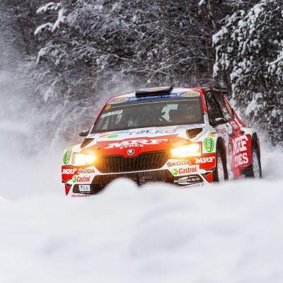 En rallybil susar fram i snön.