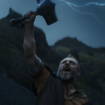 Åskguden Tor håller hammaren Mjölner ovanför sitt huvud när åskan slår ned i den.