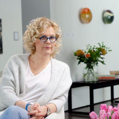 Bettina sitter i en beige fåtölj och ser rakt in i kameran. I bakgrunden står en vas med blommor på bordet och tavlor hänger på de vita väggarna.