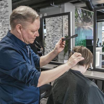 Aki Korpinen leikkaa naisen hiuksia.