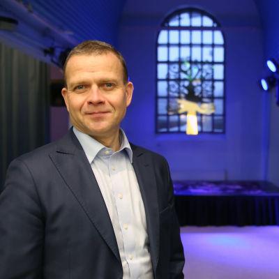 Petteri Orpo taustalla violeteilla spoteilla valaistu näyttämösali.