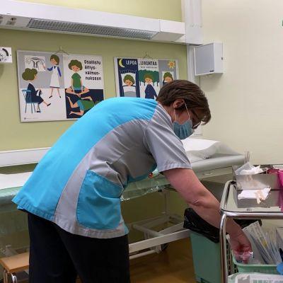 en kvinna i hälsovårdskläder och munskydd böjer sig ner i ett rum för gynekologiska undersökningar