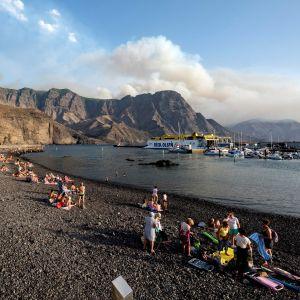 Personer på en strand på Gran Canaria betraktar röken från markbränderna.