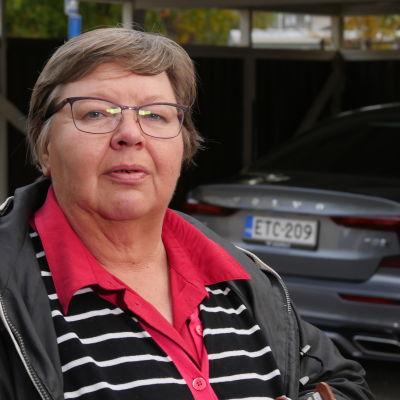 Sähköauton omistaja Tuula Toivakka . Taustalla sähköauto