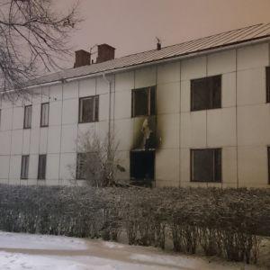 Sot efter en brand runt ett fönster på ett vitt hus.