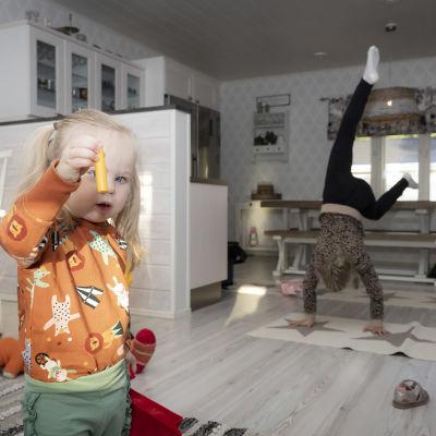 Pieni lapsi pitelee väriliitua kasvojensa edessä. Toinen, vanhempi lapsi seisoo käsillään taustalla.