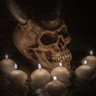 Pääkallo, jossa sarvet ja kynttilöitä ympärillä.