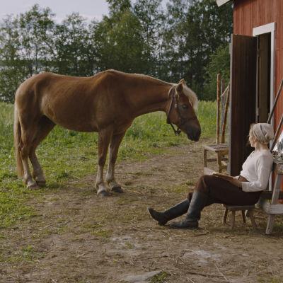 Suomen hevonen ja nainen navetan seinustalla.