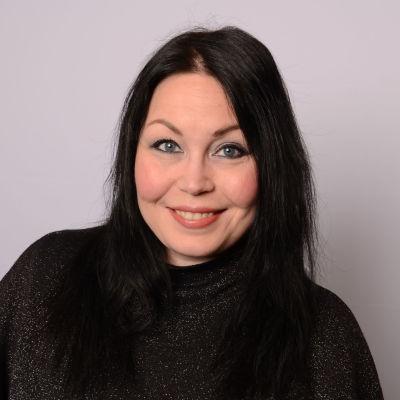 Tummatukkainen nainen tumma pusero päällään.